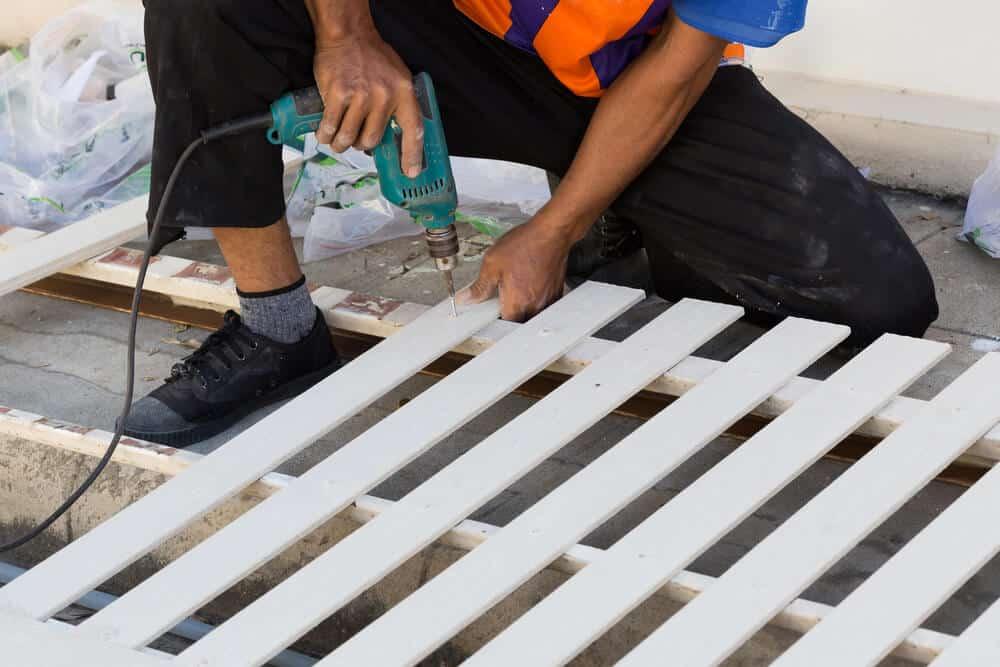 Man Installing White Fence - Big Easy Iron Works