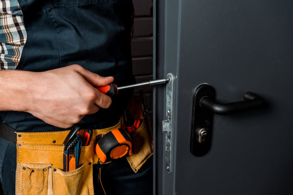 Cropped view of installer holding screwdriver near door handle | Big Easy Iron Works